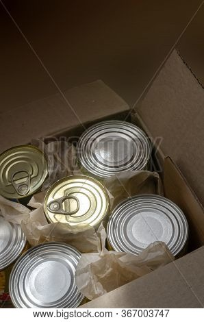 An Open Cardboard Box Full Of Tin Cans. Morning Rays Illuminate A Variety Of Canned Food In Full Tin