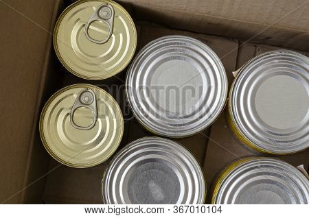 Tin Cans In A Cardboard Box. A Variety Of Canned Food In Full Tin Cans. Real Canned Food. View From