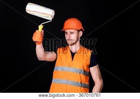 Paint And Renovate Concept. Man In Helmet, Hard Hat Holds Paint Roller, Black Background. Worker, Pa