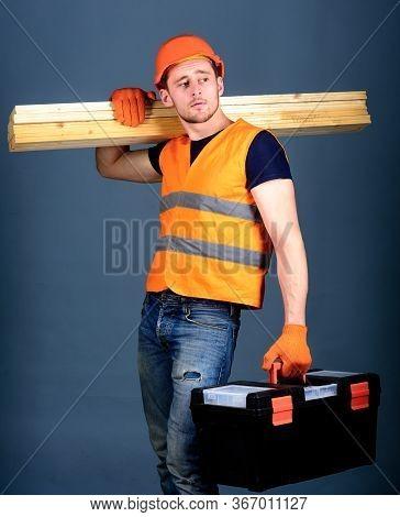 Carpenter, Woodworker, Labourer, Builder On Calm Face Carries Wooden Beams On Shoulder. Construction