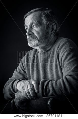 Portrait of a sad elderly pensive man in a dark room