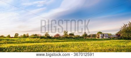 Panoramic View Of Spring Meadow With Hay Rolls On Sunset In The Village. Lithuania.