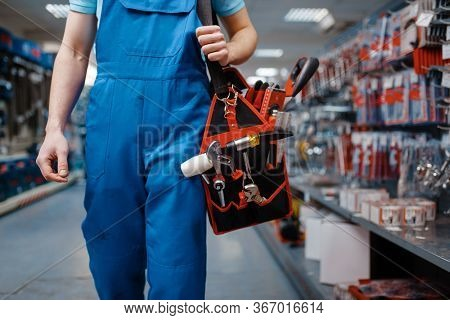 Male worker in uniform holds toolbox in tool store