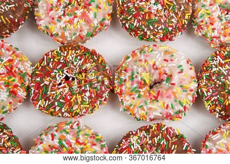 Close Up On  Cake Donuts With Sprinkles, Chocolate And Vanilla Frosting Covered In Rainbow Sprinkles
