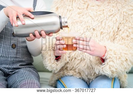 Health Conscious Teenager With Reusable Stainless Steel Water Bottle Or Tumbler Tea Pouring Tea Into