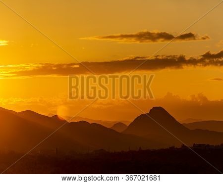 A Panorama Of The Sun Setting Behind Mountains In The Sonoran Desert Of Arizona.