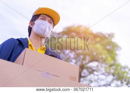 Delivery Man Employee Wearing A Face Mask And Holding Boxes Outside, Service Quarantine Pandemic Cor