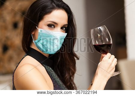 Beautiful woman holding a glass of red wine wearing a mask, coronavirus concept