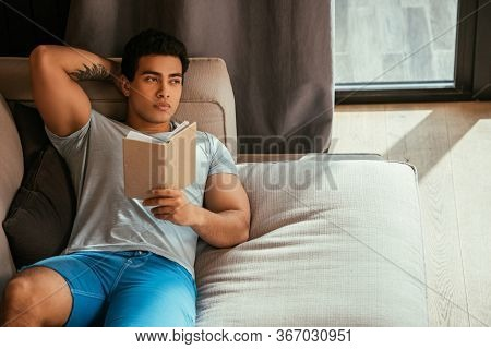 Handsome Pensive Man Reading Book While Chilling On Sofa During Self Isolation