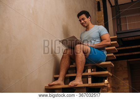 Happy Bi-racial Man Using Laptop On Stairs At Home On Self Isolation