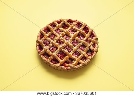 Strawberry-rhubarb Pie With A Lattice Crust On A Yellow Seamless Background. Whole Pie With Summer F