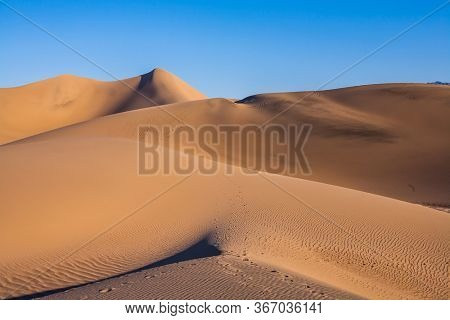 USA, California. Easily accessible dunes are located along Road 190. Magical desert morning. Mesquite Flat Sand Dunes - dunes in Death Valley. The concept of active and photo tourism