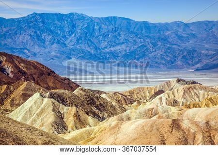 Magnificent erosion landscape of various shades. Sunset. Zabriskie Point is part of the Amargosa Range. Death Valley in California, USA. The concept of active, extreme and photo tourism