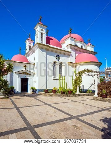 Place of worship and pilgrimage. Snow-white church building with pink domes and golden crosses. Israel, Capernaum, Lake Tiberias. The concept of religious pilgrimage, educational and photo tourism