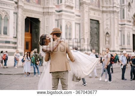 Interracial Wedding Couple. Wedding In Florence, Italy. Caucasian Groom Circles And Kisses African-a