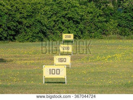 Yellow Yardage Markers And Flowers On A Texas Golf Driving Range With Green Bushes As A Backstop