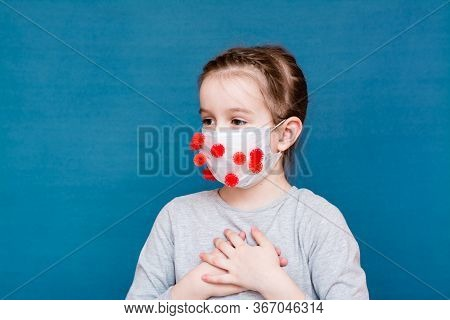 Epidemic Covid-19. Frightened Girl In A Medical Mask Covered In Coronavirus On A Blue Background.