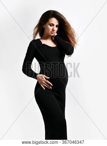 Brunette Pregnant Woman In Black Tight Dress. She Put Hand On Her Belly While Posing Sideways Isolat