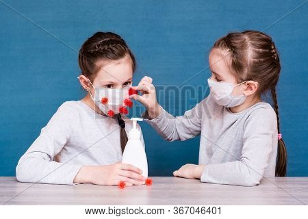 Epidemic Covert-19. Girls In Medical Masks Play With Coronavirus And Are Protected By A Sanitizer Fr