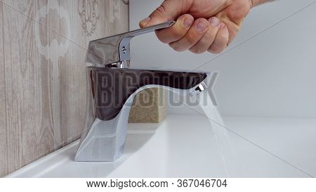 Close Up Of A Man Opening Tap At The Bathroom Sink.