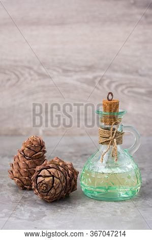 Cedar Oil In A Bottle And Cedar Cones On The Table. Treatment Of Resin Cedar. Alternative Medicine,