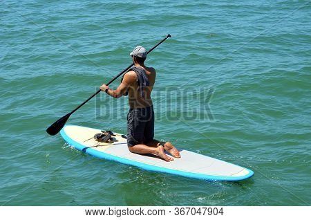 Adult Male Paddle Boarder Paddling In A Kneeling Position On An Inflatable Board Off Miami Beach On