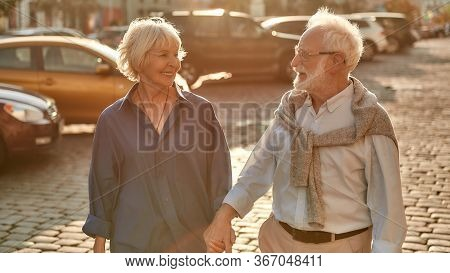 Going Home. Happy Elderly Couple Holding Hands And Looking To Each Other With Smile While Walking To