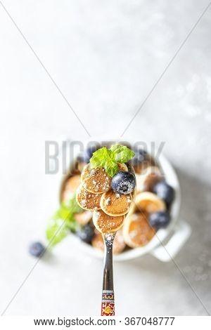Pancake Porridge. Mini Pancakes On A Spoon On A Light Concrete Background. Trendy Food Mini Pancakes