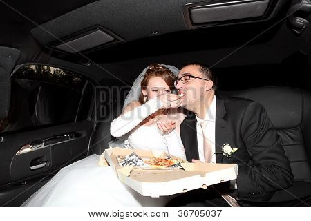 Bride And Groom Eating Pizza In The Limousine