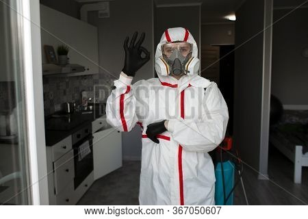 Pest Control. Worker In A Protective Suit Stands In The Background Of The Apartment And Shows Okay,