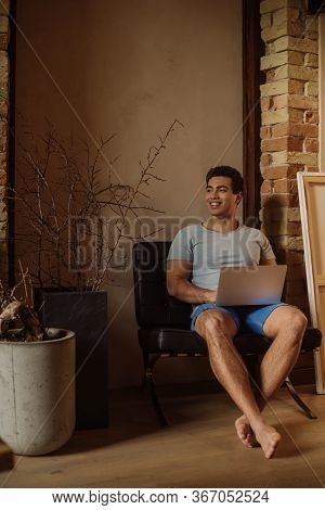 Happy Emotional Mixed Race Man Chilling With Laptop At Home During Self Isolation