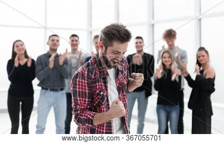 young entrepreneur standing in front of the applauding business team