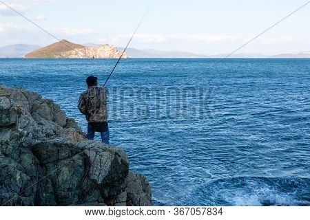 Fisherman catches fish from the rocks on the sea