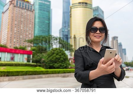 Mobile phone city lifestyle busy real estate chinese businesswoman lady texting using 5g app. Asian business woman walking in Shanghai street, China. Happy smiling person in her 50s work commute.
