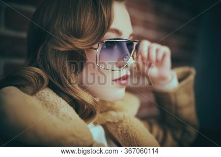 Close up portrait of a fashionable young woman in modern sunglasses. Winter style. Beauty, fashion concept. Optics, eyewear. Close-up portrait.
