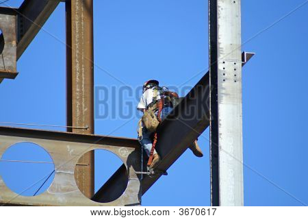 Man Working On A Skyscraper Holding On To Beam In The Blue Sky.