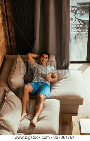 Happy Mixed Race Man Reading Book While Chilling On Sofa During Quarantine