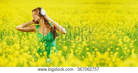 Young woman with headphones listening to music on oilseed flower field