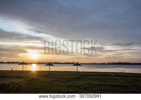 Colorful Summer Sunset On The Palic Lake, In Subotica, Serbia, While Sun Umbrella Parasols Are Visib
