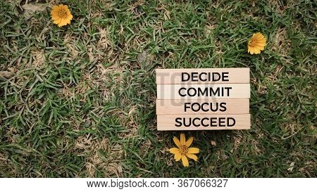 Inspirational And Motivational Words Of Decide Commit Focus Succeed On Wooden Blocks In Nature Backg