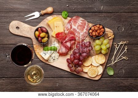 Cheese, meat, grapes and olives antipasto. Appetizer selection on wooden board and glasses with red and white wine. Top view. Flat lay