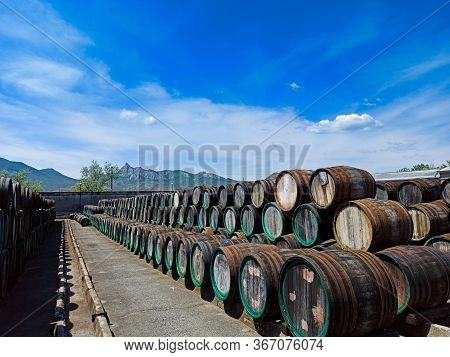 A Lot Of Oak Wine Casks With Madeira Wine While Maderization On Solarium With Mountain Background. C