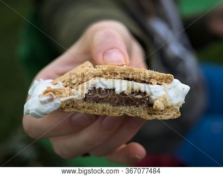 A Woman/man Hands A Perfectly Cooked Smore To The Viewer. Smore In Focus Smashed Smooshed Showing Th