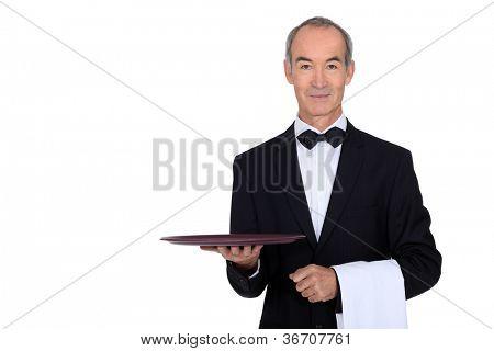 waiter in tuxedo holding a plate