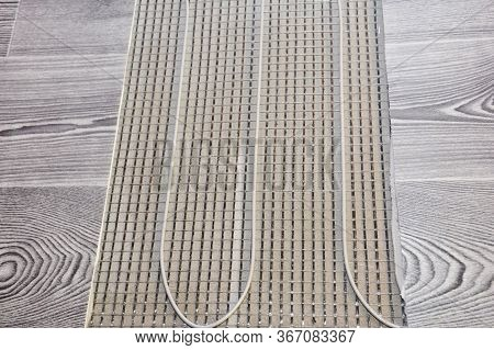 A Close Up On Electric Radiant Floor Heating System Installation Under Wood Laminate Flooring During
