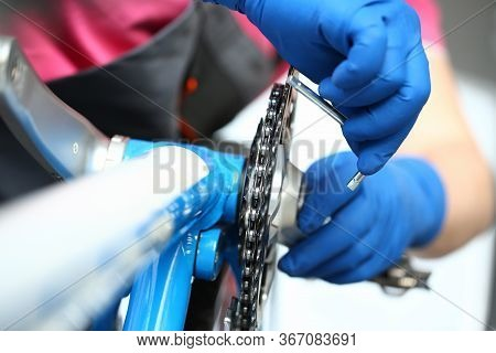 Close-up Of Mechanic Serviceman Installing Assembling Or Adjusting Bicycle Gear On Wheel In Workshop