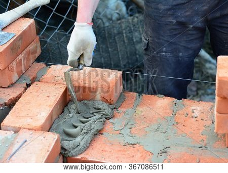 The Mason Person Is Laying Brick Wall Applying And Smoothing Cement With A Brick Trowel.