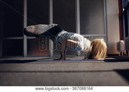 A Young Blonde Girl Practices Yoga, Does Exercises In The Gym. The Girl Does A Handstand, Lifts Her