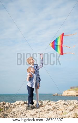 Happy Caucasian Family Little Caucasian Boy And Girl Hugging Holding Flying Multicolored Kite On Sea
