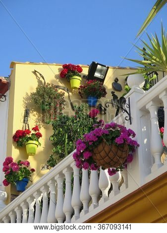 Hanging Baskets On Outdoor Light Against Yellow Painted Wall On Open Terrace Balcony In Andalusian V